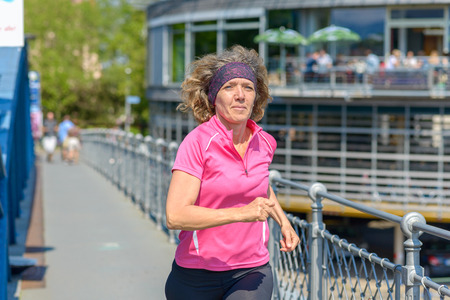 Healthy fit woman jogger running through town in spring sunshine alongside a metal railing on a bridge