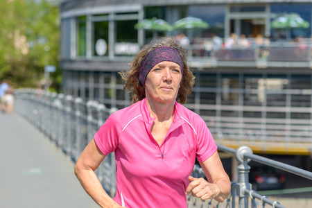 Healthy fit woman jogger running through town in spring sunshine alongside a metal railing on a bridge Banco de Imagens - 124815773