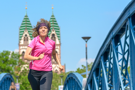 Low angle view of an Smiling woman jogging across an arched urban bridge