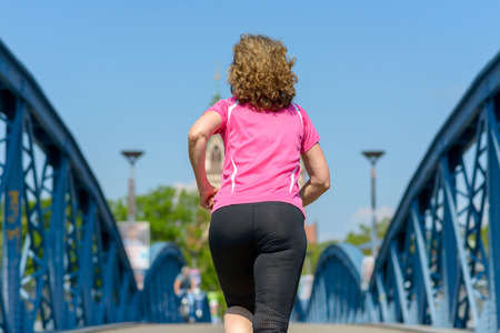 Rear view of a fit woman jogging across a blue arched bridge in urban environment conceptual of a healthy active lifestyle Banco de Imagens - 124815776