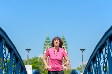 Low angle view of an Smiling woman jogging across an arched urban bridge Banco de Imagens - 124815777