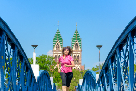 Smiling woman jogging across an arched urban bridge approaching the camera in spring sunshine in a fitness and health concept Banco de Imagens