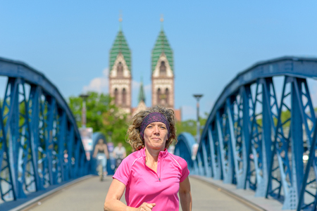 Smiling woman jogging across an arched urban bridge approaching the camera in spring sunshine in a fitness and health concept Banco de Imagens - 124815779