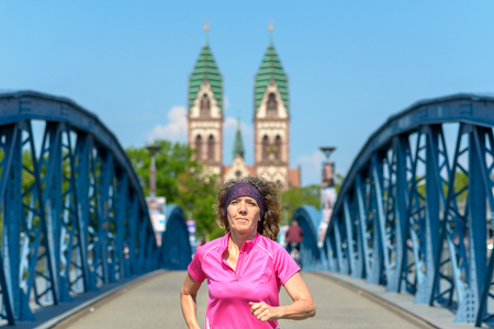 Smiling woman jogging across an arched urban bridge approaching the camera in spring sunshine in a fitness and health concept Banco de Imagens - 124815780