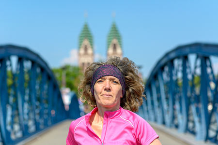 Close up of an Smiling woman jogging across an arched urban bridge approaching the camera in spring