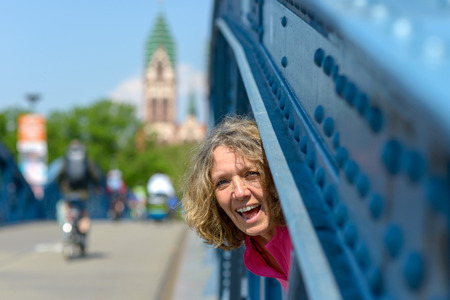Playful laughing woman peering through the blue steel girder of an arched bridge with city background Banco de Imagens - 124815785