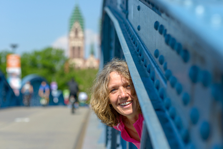 Playful laughing woman peering through the blue steel girder of an arched bridge with city background