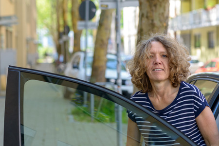 Middle-aged woman alighting from a car stepping through the open door onto the sidewalk of an urban street with a thoughtful expression
