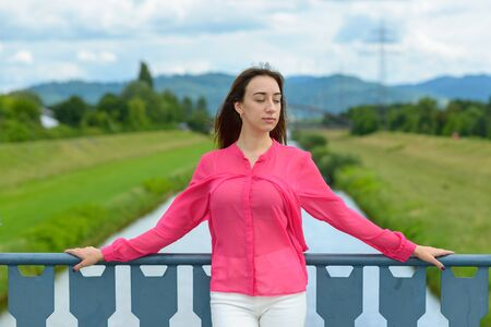 Stylish young woman standing on a bridge thinking resting her arms on the railings and closed eyes with a pensive serious expression against a rural landscape with river