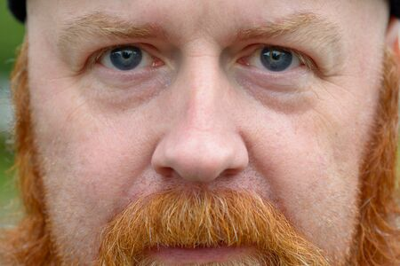 Close up cropped portrait of a redheaded man with beard and mustache wearing a beanie hat Stock Photo