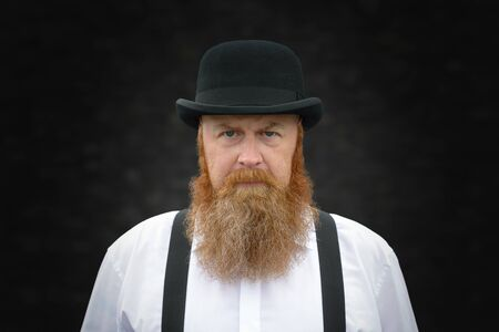 Stern bearded man in braces and bowler hat staring intently at the camera with a determined expression