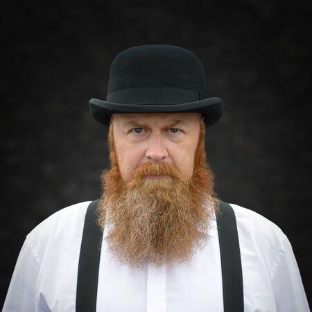 Portrait d'un homme barbu sévère à bretelles et chapeau melon regardant attentivement l'appareil photo