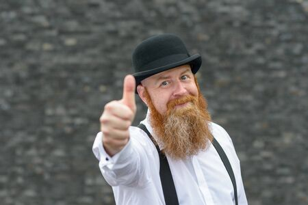 Motivated gleeful man with bushy red beard in retro bowler hat and braces giving a thumbs up gesture of success or support