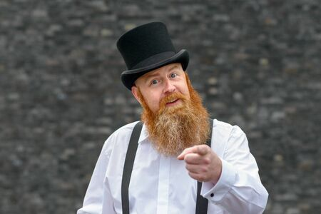 Argumentative talkative man in old fashioned top hat and braces pointing at the camera as he makes a point with persuasive expression over a grey background Stock Photo