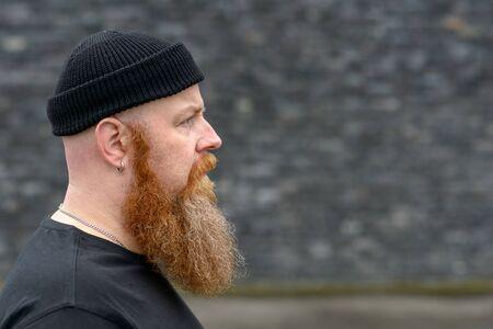 Vista de perfil de un hombre pelirrojo barbudo con un gorro que busca copiar el espacio en gris con una expresión seria y pensativa