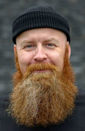 Cute charismatic redhead man with bushy beard and impish smile looking at the camera with a friendly amused expression