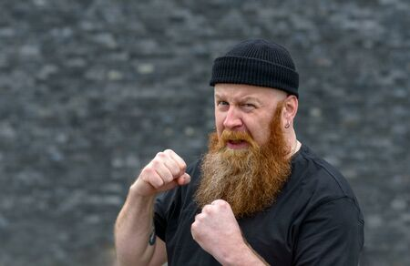 Angry aggressive man with bushy red beard in a knitted beanie hat making a fist as he snarls at the camera over grey
