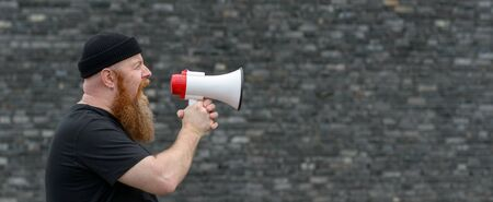 Man with a grievance yelling into a megaphone pointed to copy space at a rally, strike or demonstration in panorama banner format