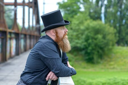 Bearded man in a top hat lost in deep thought as he stands leaning on the parapet of a bridge looking up