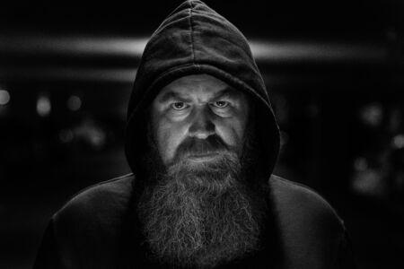Portrait sombre et sombre d'un homme barbu portant un haut à capuchon regardant attentivement la caméra avec une expression déterminée et focalisée Banque d'images