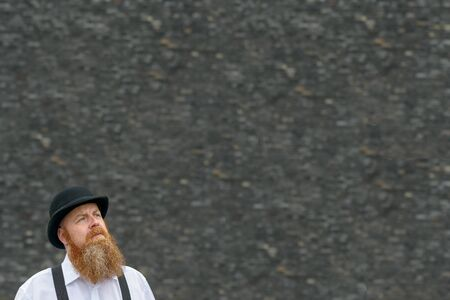 Thoughtful man with bushy red beard in bowler hat looking to big blank copy space over a textured grey background