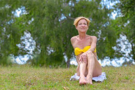 Hübsche schlanke, reife Frau in einem gelben Bikini, die auf einem Handtuch auf dem Gras vor grünen Bäumen sitzt und beiseite schaut