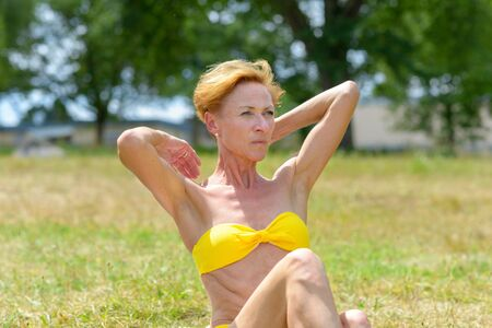 Serious attractive redhead woman in a yellow bikini sitting on grass reaching over her shoulders with her hands while looking aside