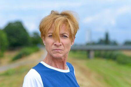 Mujer enojada molesta mirando a la cámara con una expresión intensa con su cabello rubio rojo cayendo sobre su nariz al aire libre en el campo