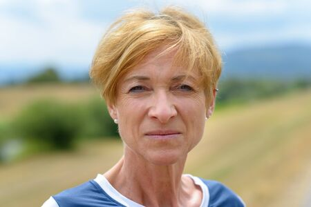 Serious pretty blond middle-aged woman staring thoughtfully at the camera in a close up head shot on a quiet rural road in summer Stock Photo
