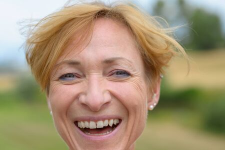 Happy woman with a lovely vivacious smile and modern short red blond hair in a close up head shot outdoors in countryside Banco de Imagens