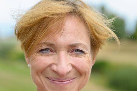 Mujer feliz con una encantadora sonrisa vivaz y moderno cabello rubio rojo corto en un primer plano disparo a la cabeza al aire libre en el campo