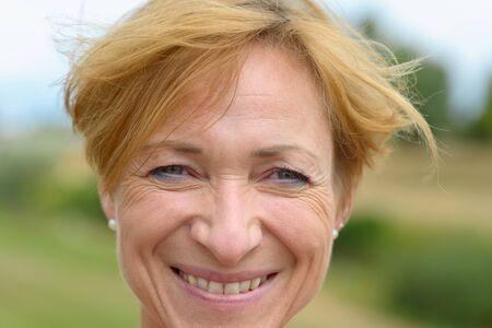 Mujer feliz con una encantadora sonrisa vivaz y moderno cabello rubio rojo corto en un primer plano disparo a la cabeza al aire libre en el campo Foto de archivo