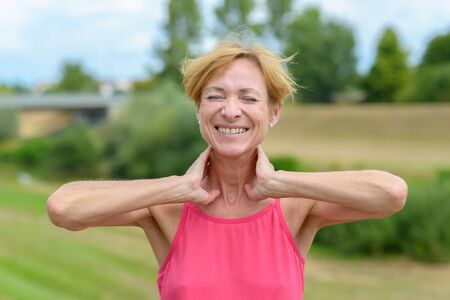 Happy sporty woman stretching with hands to her neck, closed eyes and a beaming smile of appreciation outdoors in a rural landscape