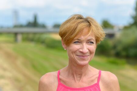 Happy woman smiling to herself as she watches off to the right side of the frame outdoors in sunny countryside in summer
