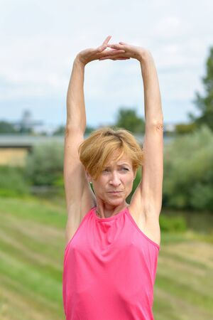 Serious vivacious woman stretching her arms above her head as she rejoices outdoors in summer sunshine Banco de Imagens