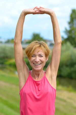 Happy vivacious woman stretching her arms above her head while laughing at the camera as she rejoices outdoors in summer sunshine