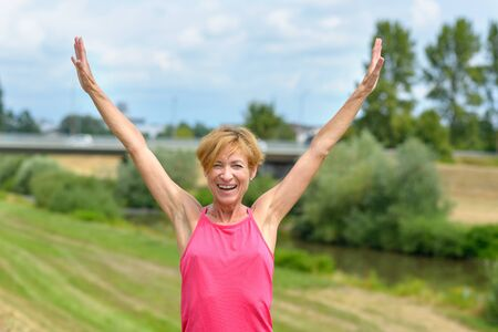 Happy enthusiastic woman rejoicing the summer sun flinging her arms in the air and laughing outdoors in the countryside Banco de Imagens