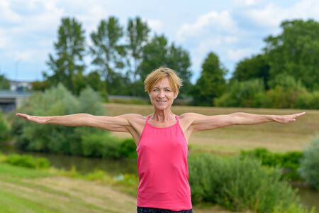 Fit healthy slender middle-aged woman holding out her arms to the side in a colorful pink sports top outdoors in countryside Banco de Imagens