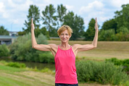 Happy fit slender woman in sportswear doing yoga posing with raised arms looking at the camera with a friendly smile outdoors in summer countryside