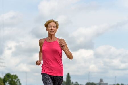 Fit healthy woman working out jogging outdoors under a cloudy sky in a low angle view as she approaches