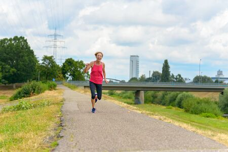 Athletic fit woman jogging on a rural road laughing as she approaches the camera in a health, fitness and freedom concept