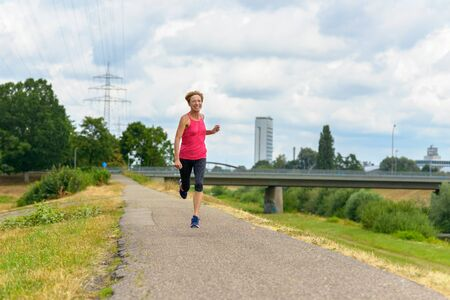 Athletic fit woman jogging on a rural road laughing as she approaches the camera in a health, fitness and freedom concept Stock fotó