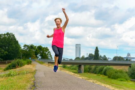 Energetic motivated exuberant middle-aged woman running along a quiet rural road leaping and cheering as she laughs at the camera in a low angle view