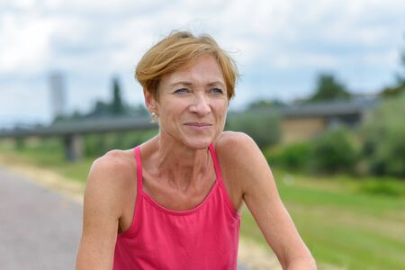 Close up of a athletic woman squatting for a rest after a workout jogging along a rural road