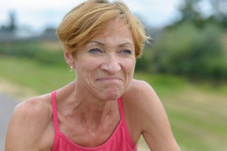 Middle-aged woman grimacing with a wry expression as she stands outdoors in summer in the countryside in a close up portrait Banco de Imagens