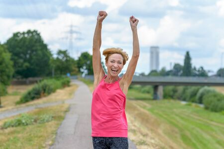 Exuberant vivacious woman celebrating outdoors laughing and raising her arms in the air on a quiet country road