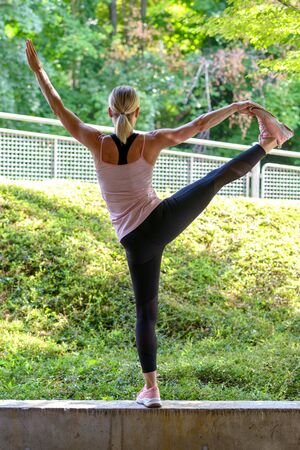 Woman practicing yoga or pilates outdoors standing on a wall balancing on one leg facing away from the camera over greenery