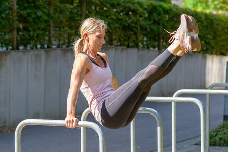 Full length side view of an athletic young woman raising her legs from handstand position on two parallel bars outdoors in a sunny day Banco de Imagens