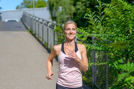 Close up of a young fit and determined woman smiling happy while jogging outdoors in a sunny day of summer