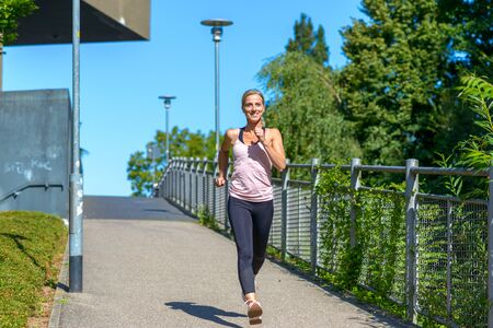 Full length view of a young fit and determined woman smiling happy while jogging outdoors in a sunny day of summer